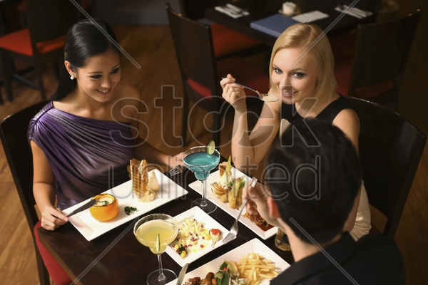 man and women having dinner together stock photo