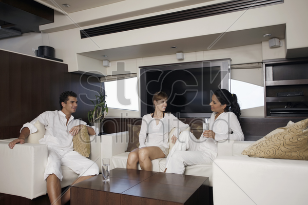 man and women relaxing in yacht living room stock photo