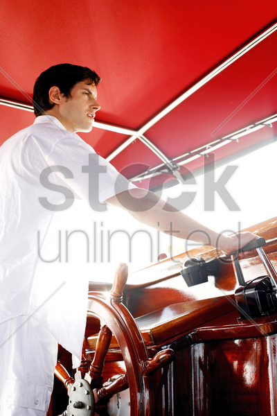 man at helm of yacht stock photo