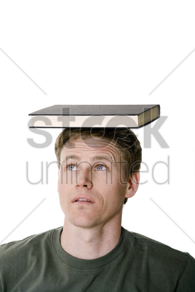 man balancing a book on his head stock photo