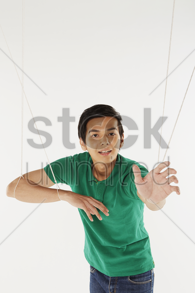 man being pulled by strings, like a puppet stock photo