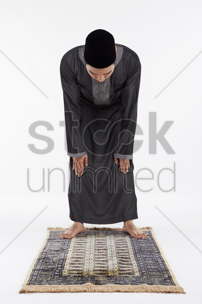 man bending at the waist until his palms touch his knees, staying still stock photo