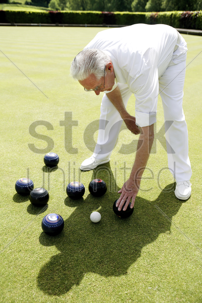 man bending down to pick up bowling balls stock photo