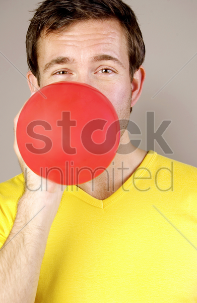 man blowing a red balloon stock photo