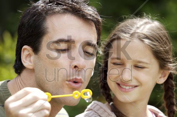 man blowing bubbles with wand while girl looking on stock photo