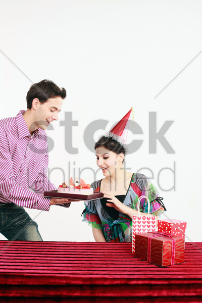 man bringing out a surprise birthday cake for woman stock photo