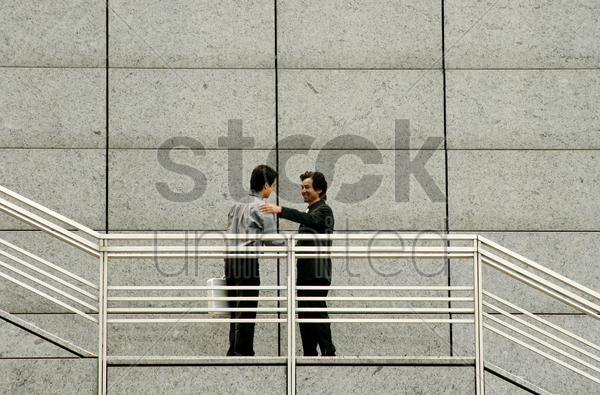 man bumping into his friend while using the stairs stock photo
