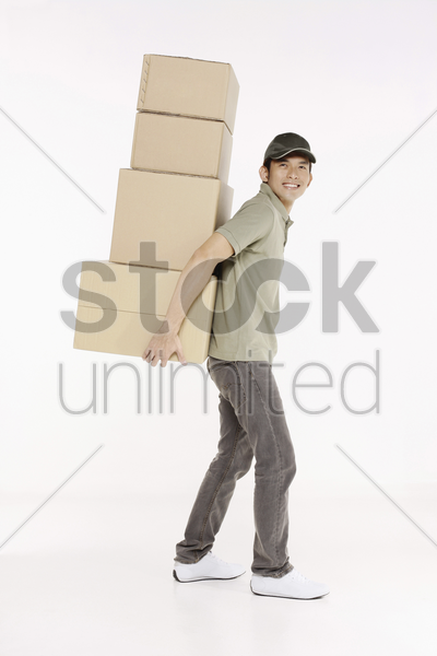 man carrying a stack of packages stock photo