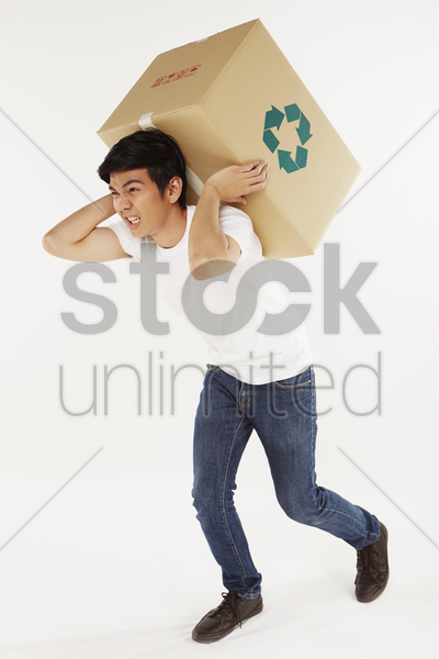 man carrying a very heavy recyclable box stock photo