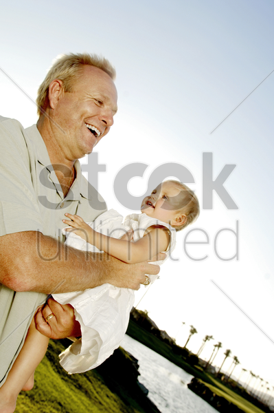 man carrying a young girl stock photo