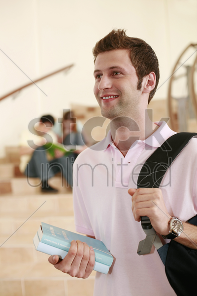 man carrying backpack while two people are having discussion in the background stock photo
