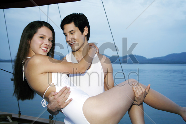 man carrying his girlfriend stock photo