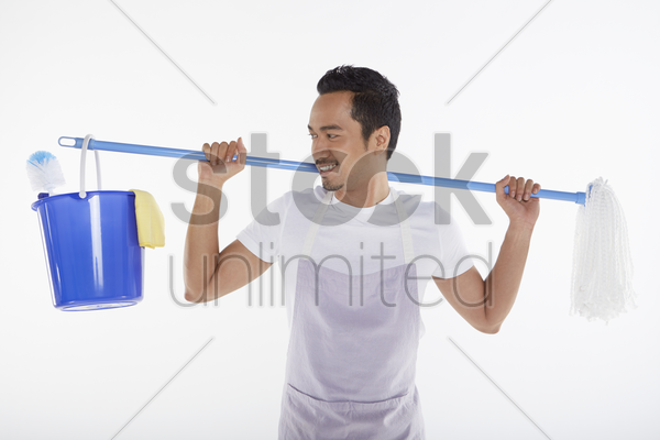 man carrying mop and bucket on his back stock photo