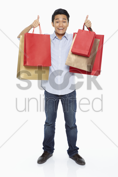 man carrying shopping bags and showing hand gesture stock photo