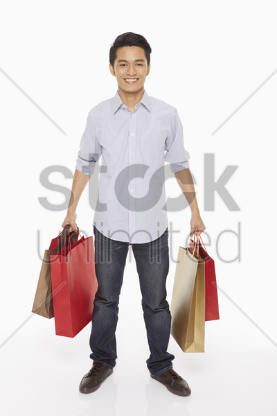 man carrying shopping bags stock photo