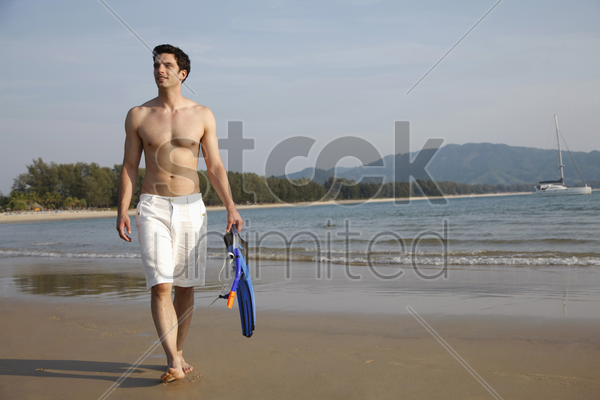 man carrying snorkeling gear stock photo