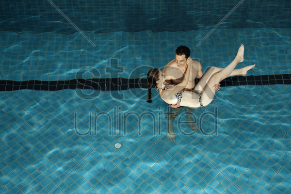 man carrying woman in swimming pool stock photo