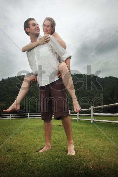 man carrying woman on his back stock photo