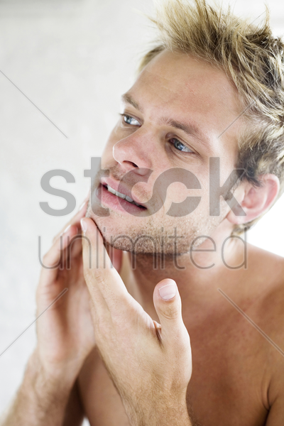 man checking his face in the mirror stock photo