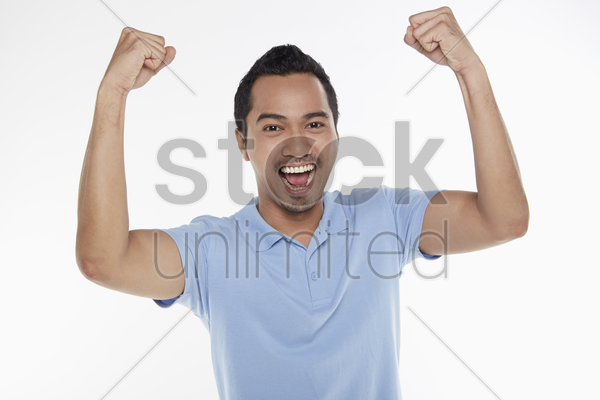 man cheering with fist in the air stock photo