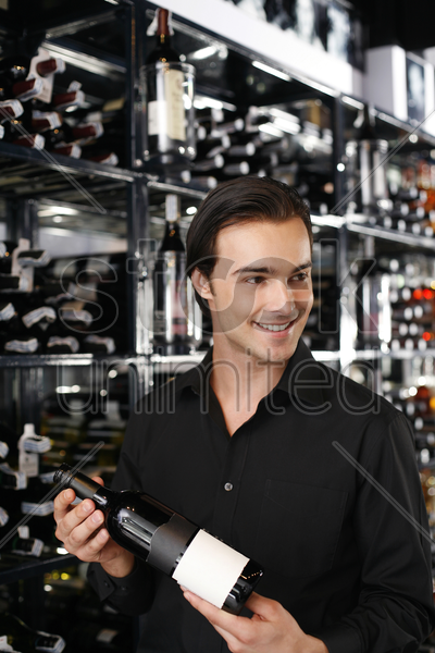 man choosing a bottle of wine from the wine cellar stock photo