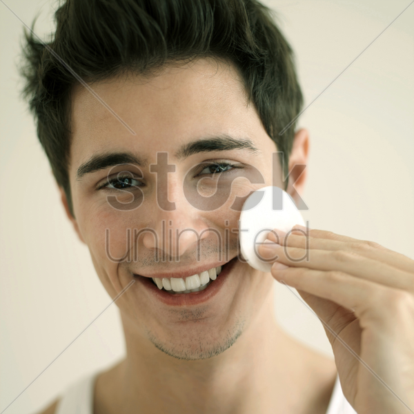 man cleaning his face with cotton stock photo