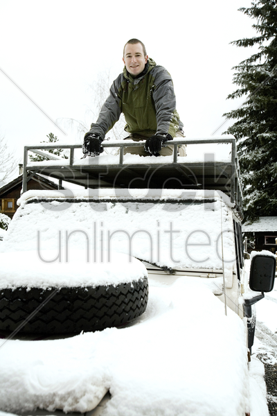 man climbing on the top of jeep stock photo