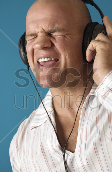 man closing his eyes while listening to music on the headphones stock photo