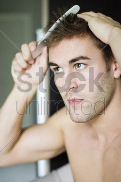 man combing his hair stock photo
