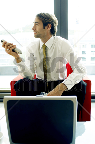 man controlling the air-conditioner with a remote control stock photo