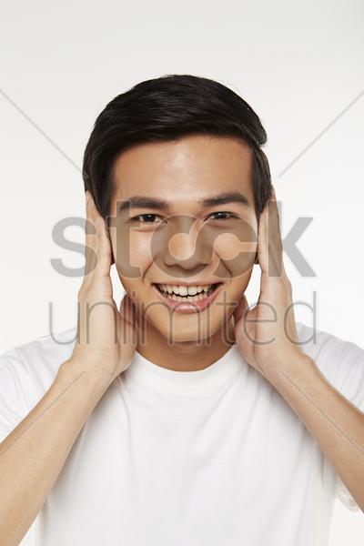 man covering ears with hands stock photo