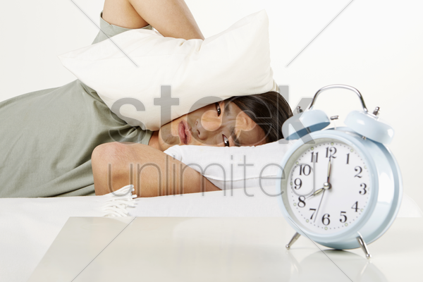 man covering ears with pillow stock photo