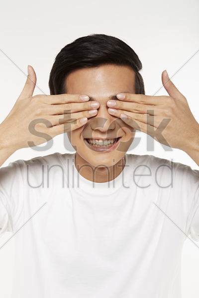man covering eyes with hands stock photo
