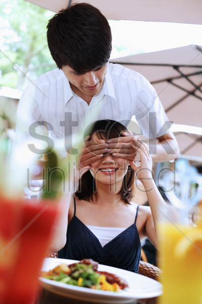 man covering woman's eyes with hands stock photo
