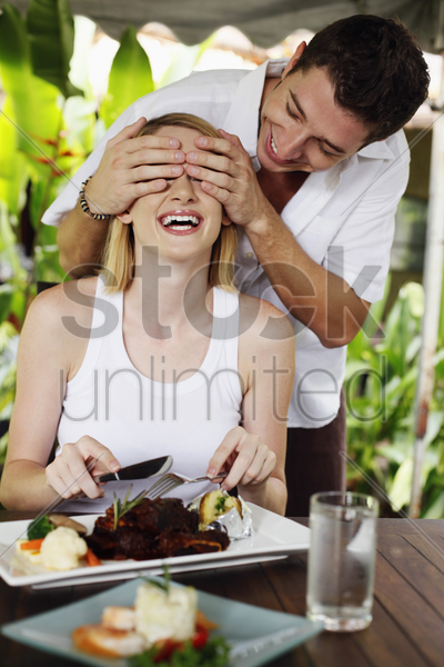 man covering woman's eyes stock photo