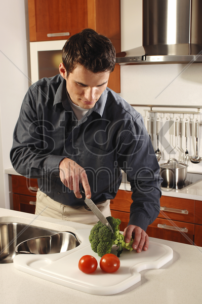 man cutting vegetables in the kitchen stock photo