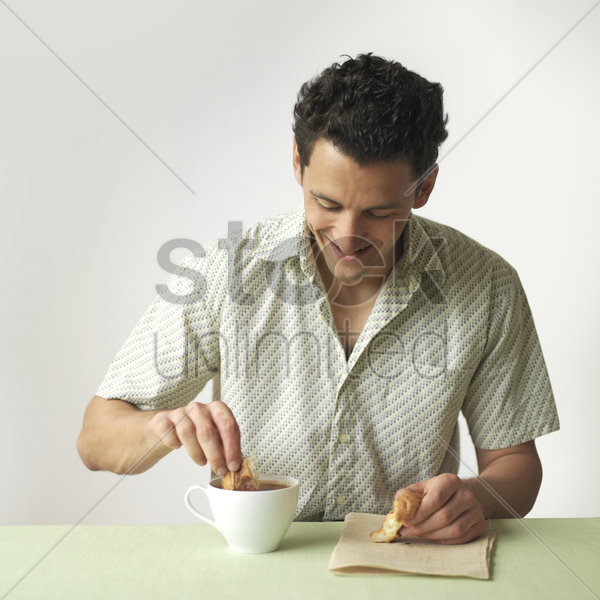 man dipping croissant into a cup of coffee stock photo