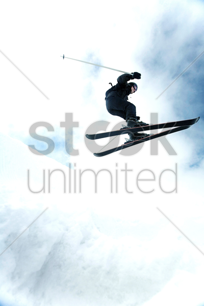 man doing a mid air ski jump off a mountain stock photo
