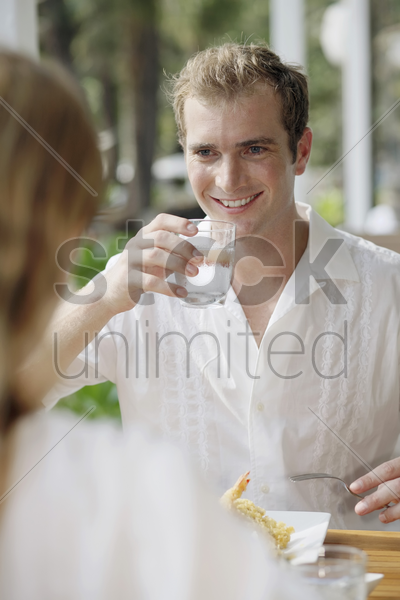 man drinking a glass of water stock photo