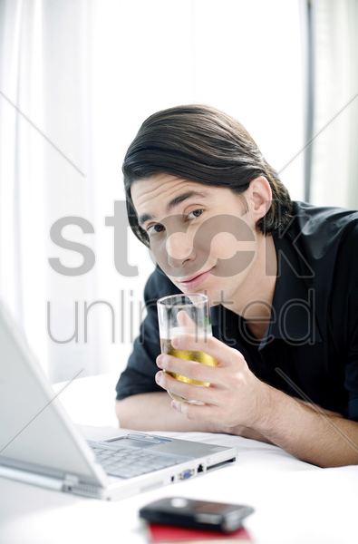 man drinking beer while using laptop stock photo