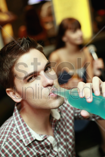 man drinking bottled drink stock photo