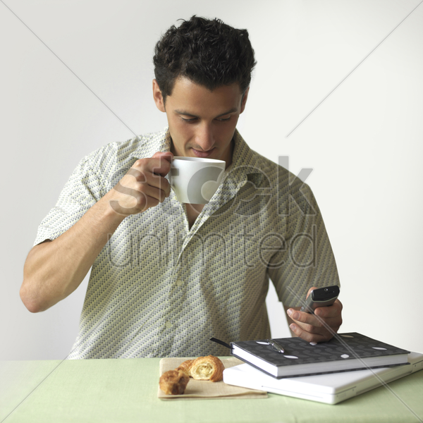 man drinking coffee while text messaging on the mobile phone stock photo