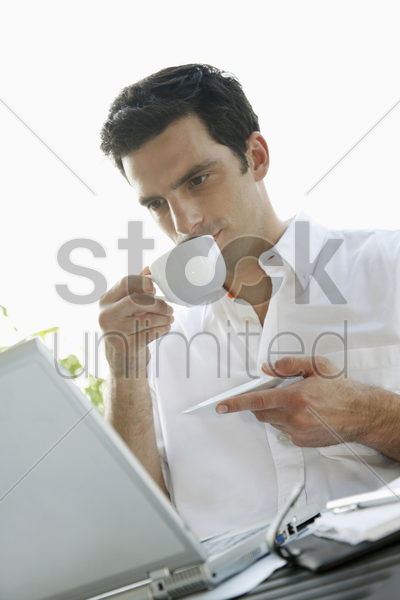 man drinking coffee while using laptop stock photo