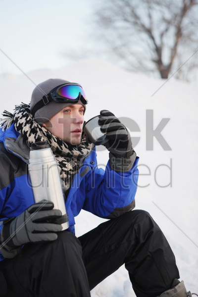 man drinking hot water on winter day stock photo