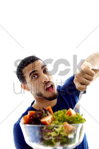 man eating a bowl of salad stock photo