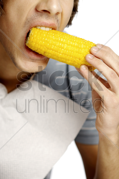 man eating corn on cob stock photo