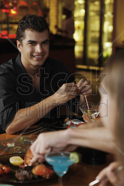 man eating with friends in a restaurant stock photo