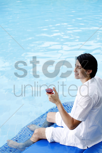 man enjoying a glass of red wine by the pool side stock photo