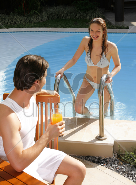 man enjoying drink by the pool side with his girlfriend climbing out from the pool stock photo