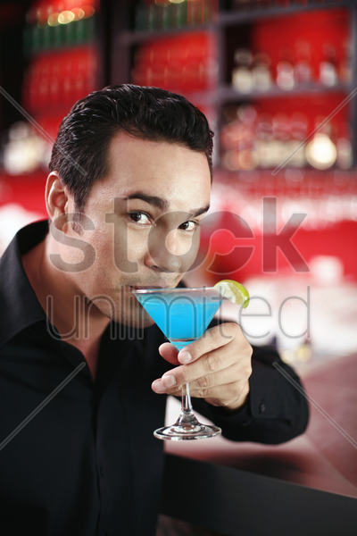 man enjoying his glass of cocktail stock photo
